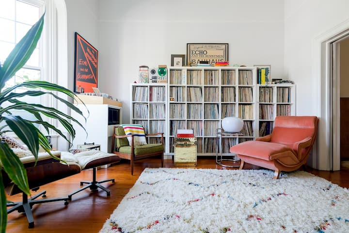 A living room with wooden floors and tall windows. Main focal points include a textured rug and a large record collection against the back wall. Framed music posters hang on the walls, and there are three cushioned armchairs of various sizes and textures.