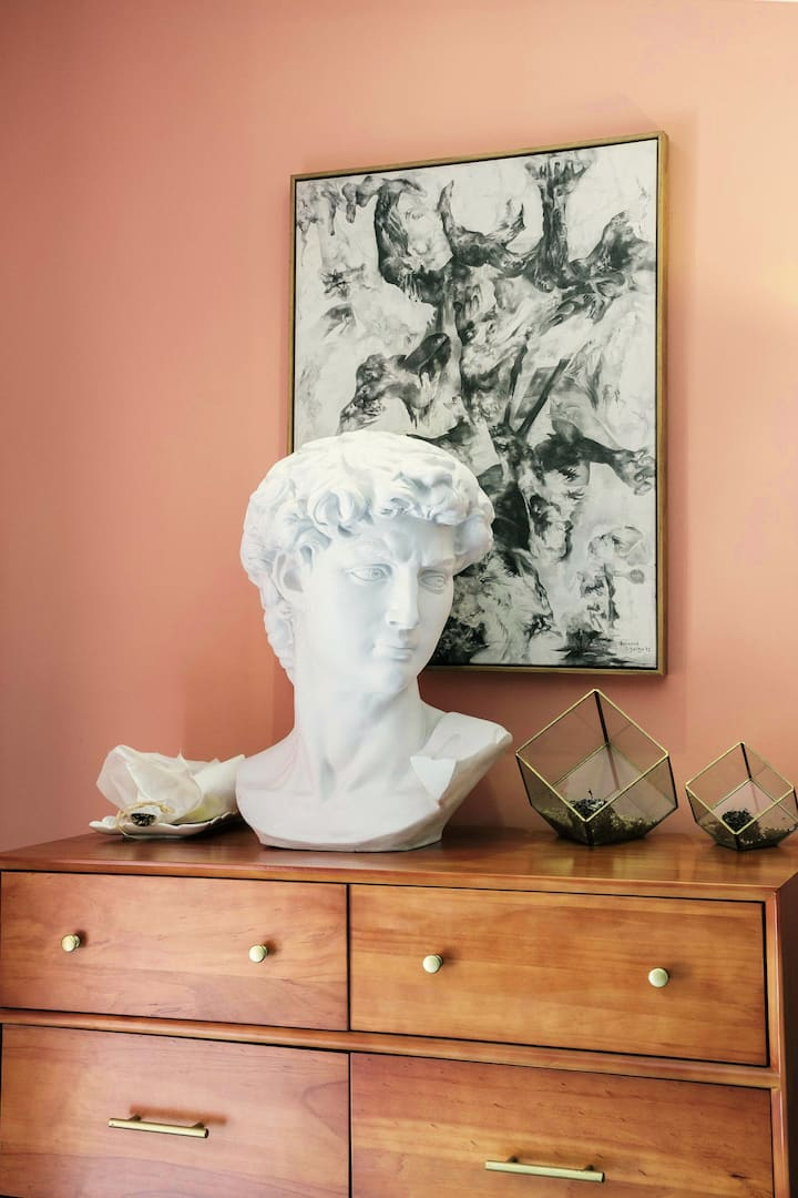 A decorative bust and two geometric glass terrariums rest on top of a modern wooden dresser. The dresser is pushed against a light pink wall on which a framed piece of abstract art is hung.
