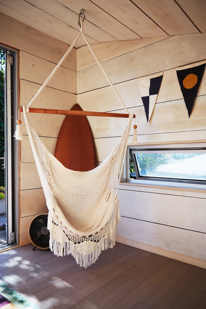 A woven hammock chair hangs from the ceiling near a small window and a door leading to an outdoor area. Above the window on the wooden wall to the right hangs a triangle flag garland.