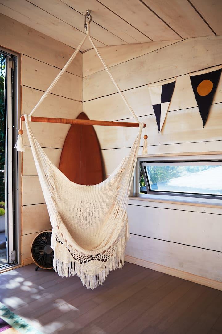Una hamaca tejida cuelga del techo cerca de una ventanita y una puerta, que conduce a un área exterior. Sobre la ventana situada en la pared de madera, a la derecha, cuelga una guirnalda de banderines triangulares.