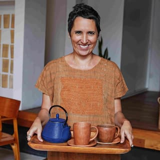 A smiling woman with brown, closely cropped hair holds a tray with a teapot and tea cups.