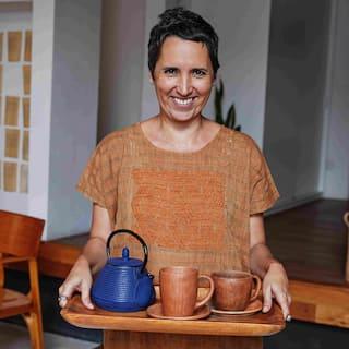 Una dona somrient, amb els cabells ben curts i de color castany, porta una safata amb una tetera i unes tasses de te.