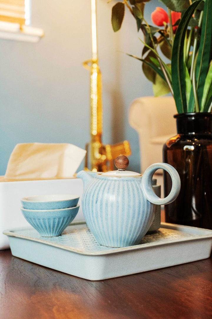 A blue ceramic teapot and matching tea cups are stacked atop a wooden table next to a stylish box of tissues and an amber glass vase with fresh flowers. In the background is a plush armchair and a drape-covered window.