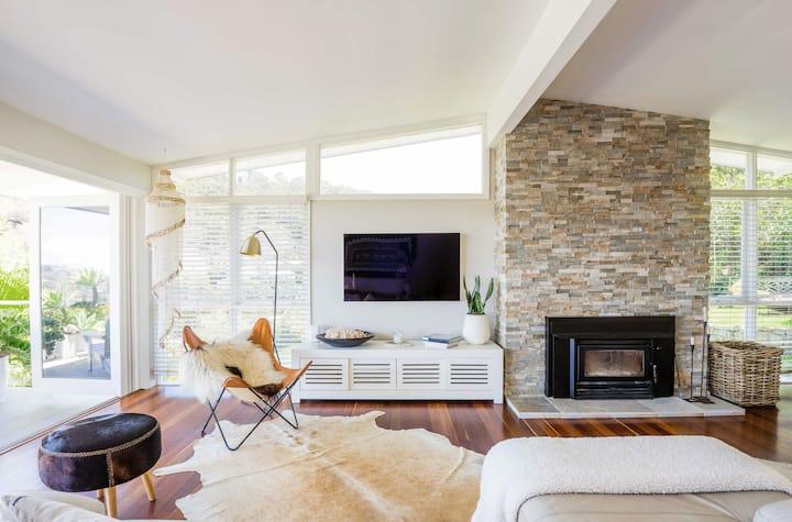 Светла дневна соба во модерен стил од средината на 20-от век, со заоблен таван, прозорци од под до таван и лизгачка стаклена врата што води кон дворот. Во позадината има прозорци, камин изработен од камен и телевизор прикачен на ѕид. Подот е покриен со килим од кравја кожа, а собата е опремена со кожна фотелја и отоман.