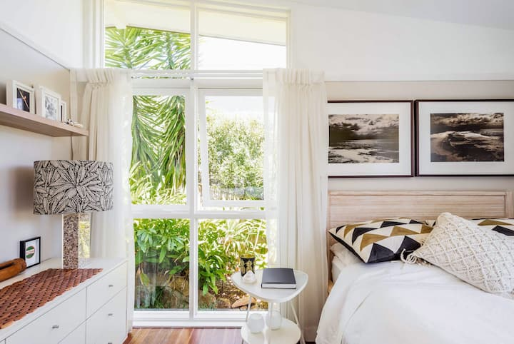Bright corner of a bedroom with white walls, framed artwork, and a small bedside table. White drapes partially cover floor-to-ceiling windows, one pane of which is slightly opened.
