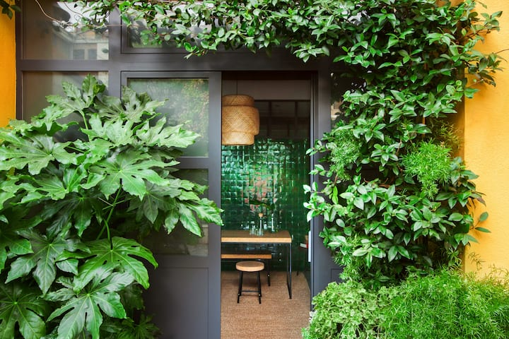Leafy palm, fern, and ivy plants adorn a gray glass-and-steel exterior wall with an entry into an indoor dining area. Through the door is a room with a green-tiled wall, a woven area rug, and a woven pendant lamp hanging above a wooden dining table set with a glass carafe full of water.