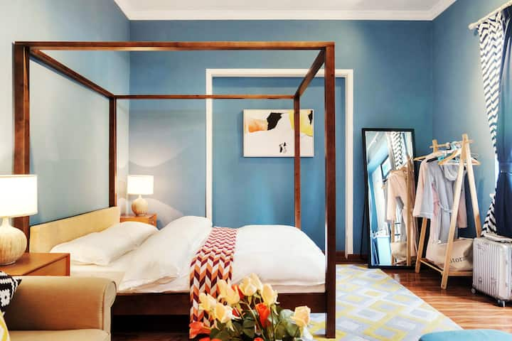 A blue-walled bedroom with wooden floors covered by a large area rug. To the right is a curtain-trimmed window. Dominating the room is a wooden four-poster cube bed flanked by two wooden side tables with small lamps. A plush armchair sits in one corner closest to the bed, and in the opposite side of the room is a full-length mirror and wooden clothing rack.