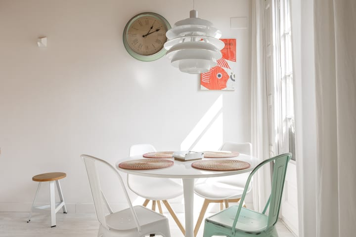 A sunlit breakfast corner with an olive wall clock, three white chairs, and an olive chair.