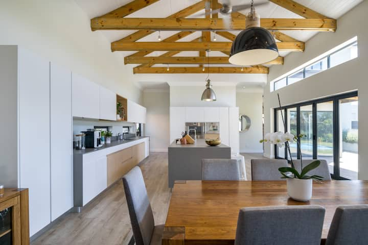 An open dining room and kitchen with wooden rafters and a modern, wooden table.