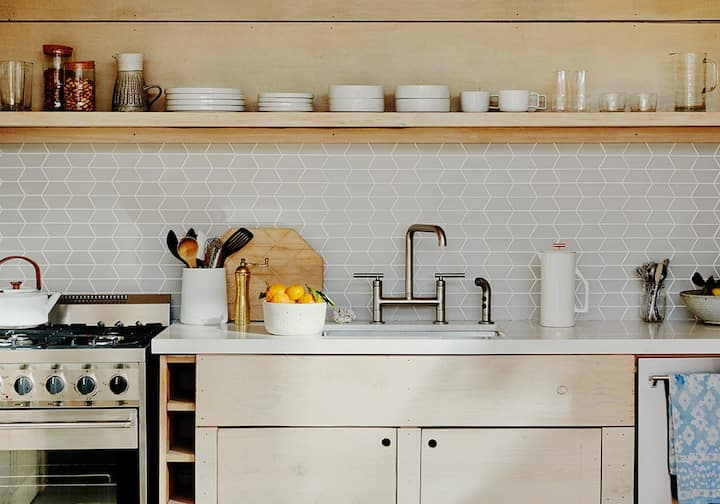 A white and wooden kitchen is neatly arranged with lemons, glass jugs and ceramic saucers.