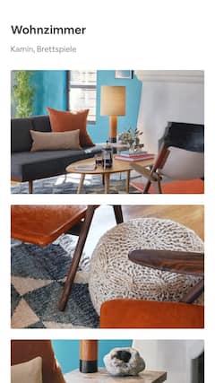 Ein sonniges Wohnzimmer mit modernen Möbeln, das Mahagoni-Detail einer Stuhl-Armlehne und eine Geode auf einem hölzernen Beistelltisch.