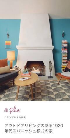 リビングルームにある青と赤のモダンな家具、木製のコーヒーテーブル、きれいに積み上げられた本。
