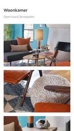 Een zonnige woonkamer met moderne meubels, de mahoniehouten leuning van een stoel en een geode op een houten bijzettafel.