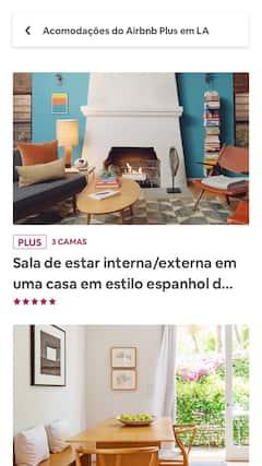 Uma sala de estar com móveis modernos e uma cozinha bem iluminada e arejada.