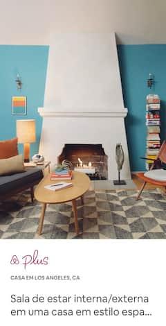 Uma sala de estar com móveis modernos em azul e vermelho, uma mesa de centro de madeira e uma pilha de livros alta e organizada.