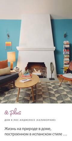В гостиной современная мебель в синих и красных тонах, деревянный кофейный столик и большая аккуратная стопка книг.