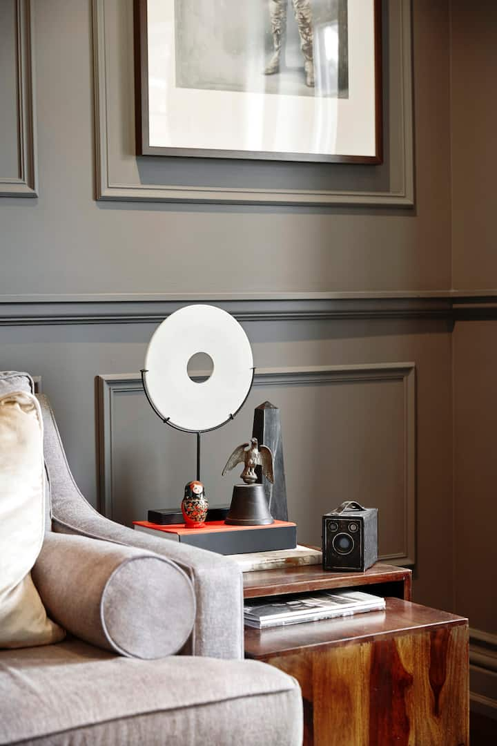 In the living room is a panelled wall mounted by a piece of framed artwork. In the foreground we see the left edge of a gray couch, and a wood side table covered with books, an old-fashioned Brownie camera, and small sculptural objects.