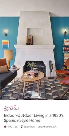 Una sala d'estar amb mobles moderns de color blau i vermell, una tauleta de fusta i una gran muntanya de llibres ben apilats.