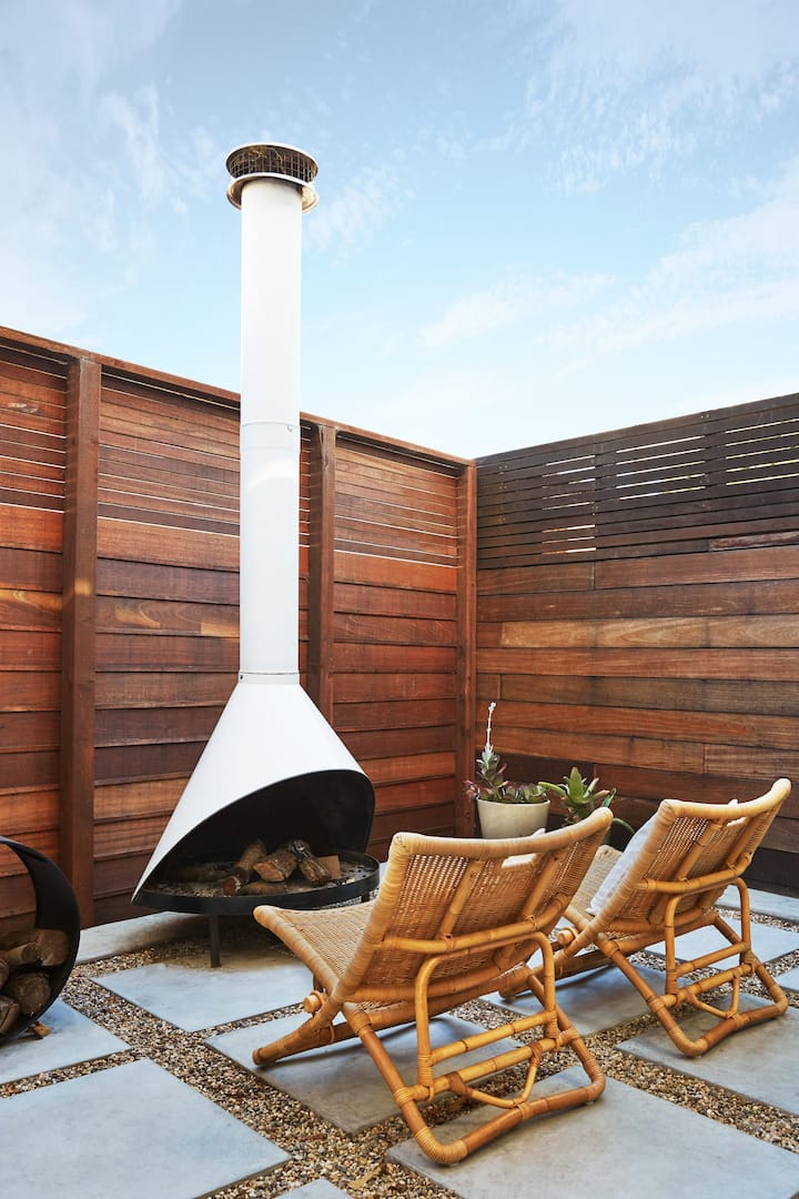 A high wooden fence provides privacy for the small outdoor patio, equipped with two woven chairs and an outdoor fireplace.