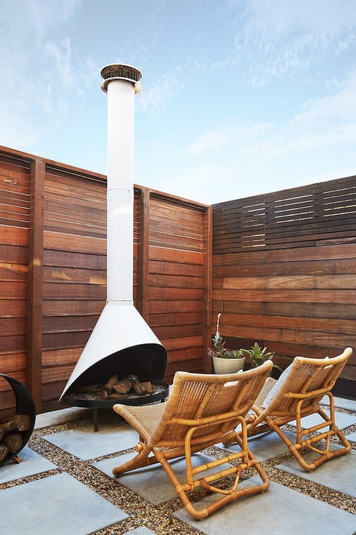 Una valla de madera elevada ofrece privacidad al pequeño patio exterior, equipado con dos sillas tejidas y una chimenea al aire libre.