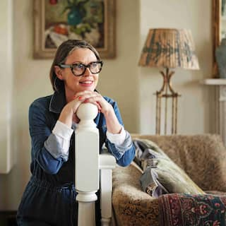 A woman wearing eyeglasses rests her head and hands on a railing. In the background, a painting of a vase and flowers hangs on a cream-colored wall, and to her right sits a beige, patterned couch and floorlamp with a golden metal base and a black and beige patterned lampshade.