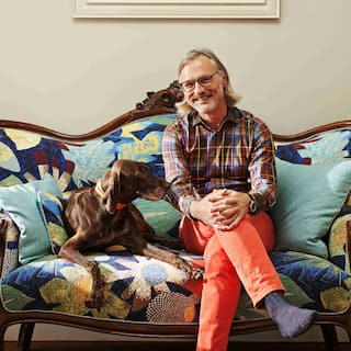 A smiling man with glasses and shoulder-length gray hair sits beside a brown dog on a floral patterned couch.