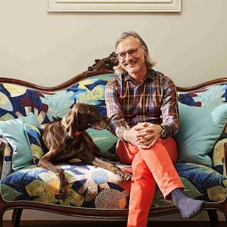 Un home somrient, amb ulleres i cabells grisos fins a les espatlles, seu al costat d'un gos marró en un sofà amb un estampat de flors.