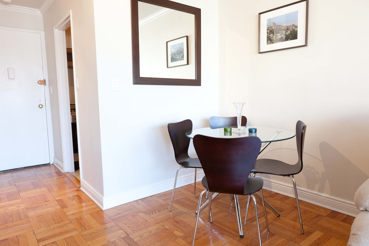 Glasstop table with four chairs in living room.