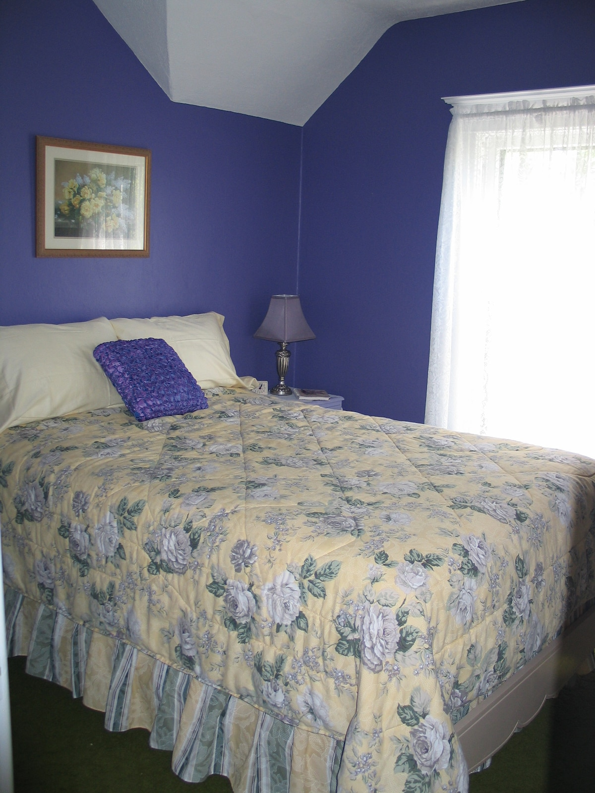 The purple room is bright & cheerful with a south facing window overlooking the large back yard