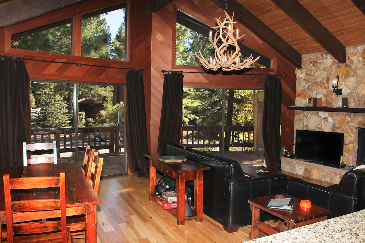 High vaulted ceilings in the living/dining area with floor to ceiling windows looking out to the large deck