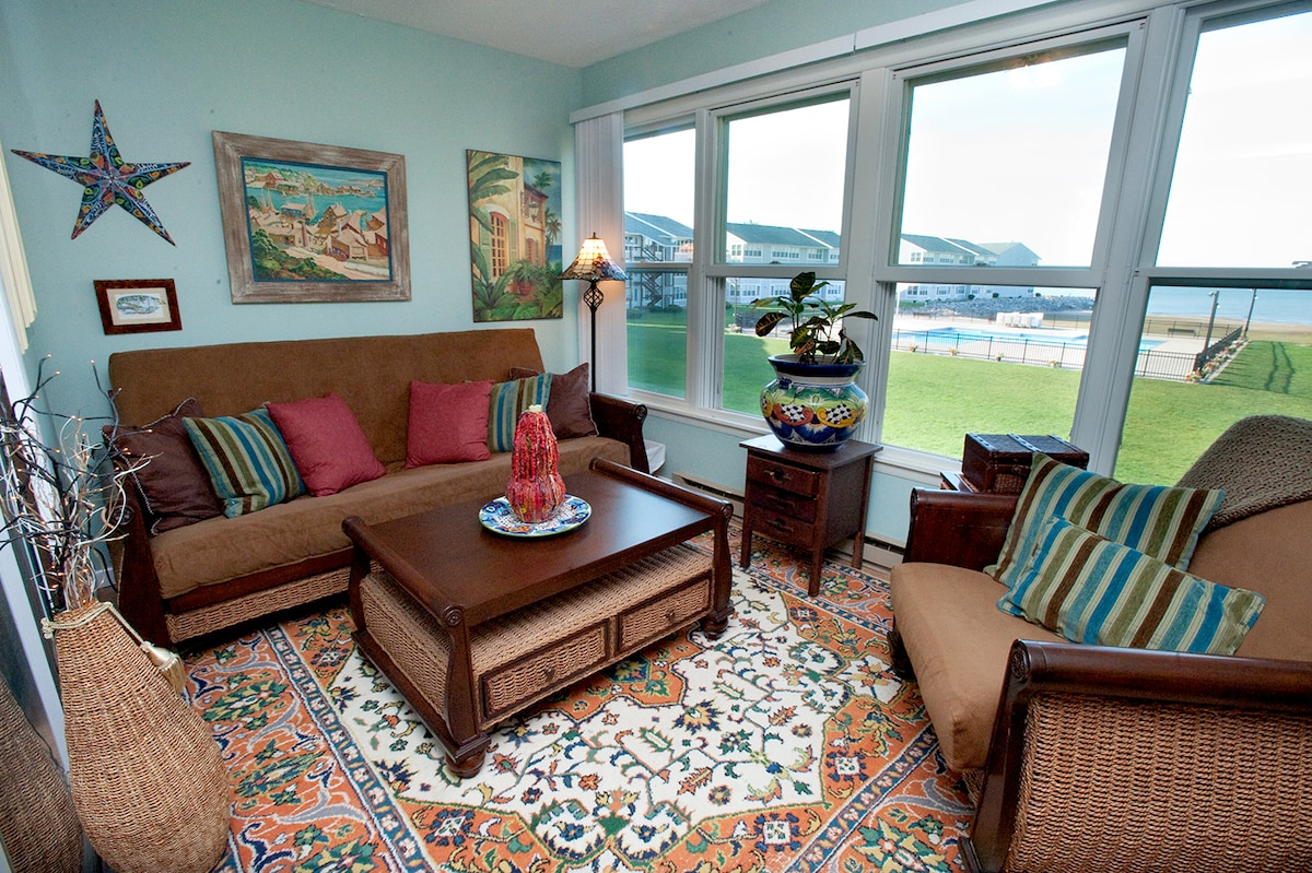 The warm and inviting sunroom has a sweeping view of the pool and the beach!