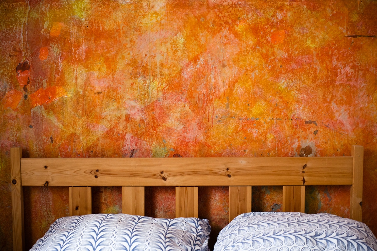 bedroom with a rough wall in red shade