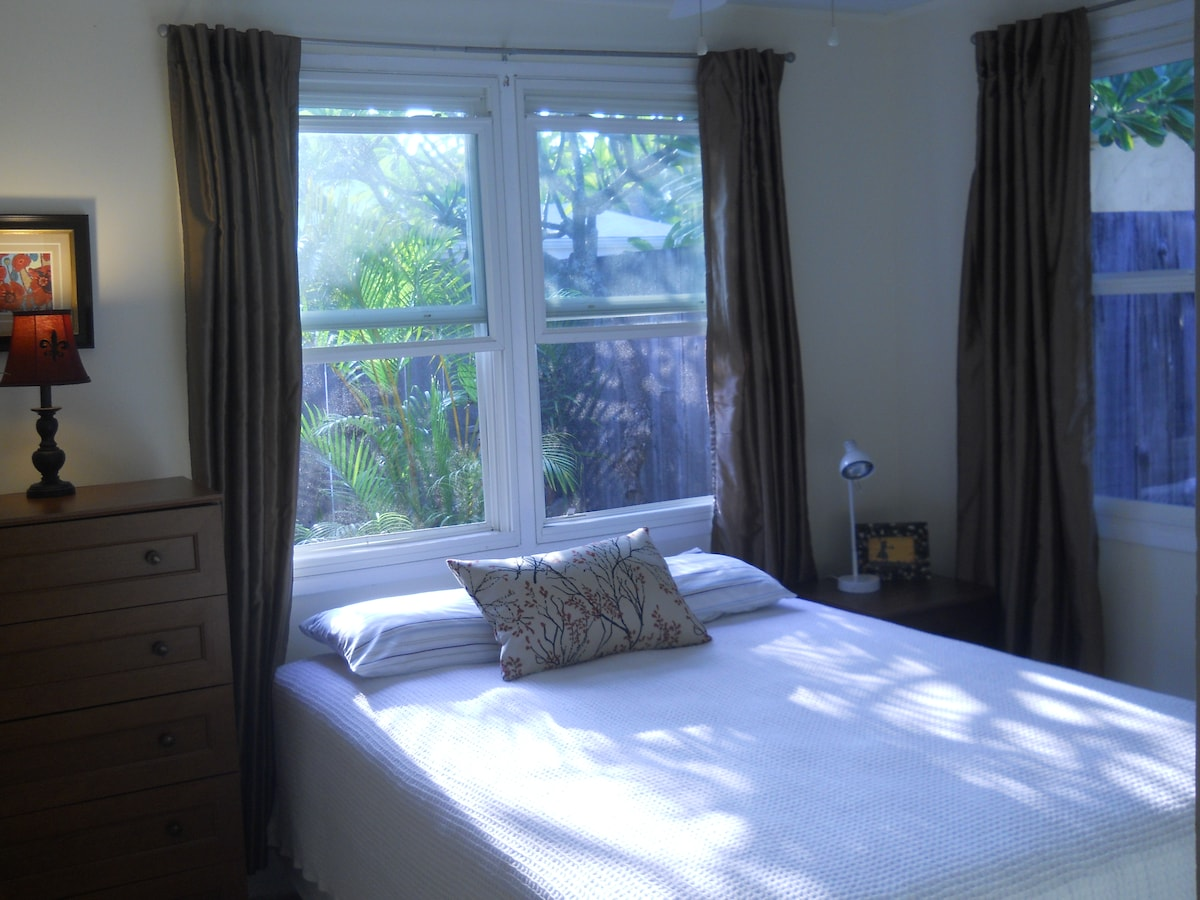 Small bedroom has a queen size bed and looks into the water fountain garden.