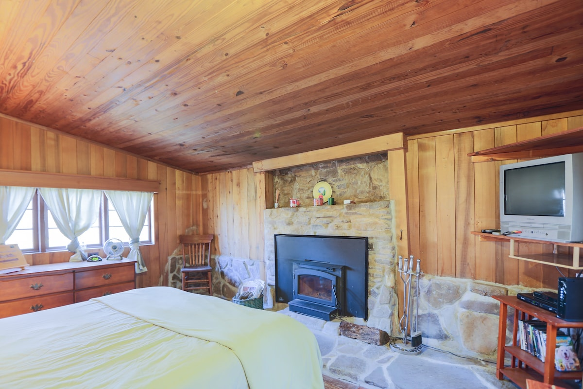Bedroom with wood burning fireplace. We provide the firewood too for free.