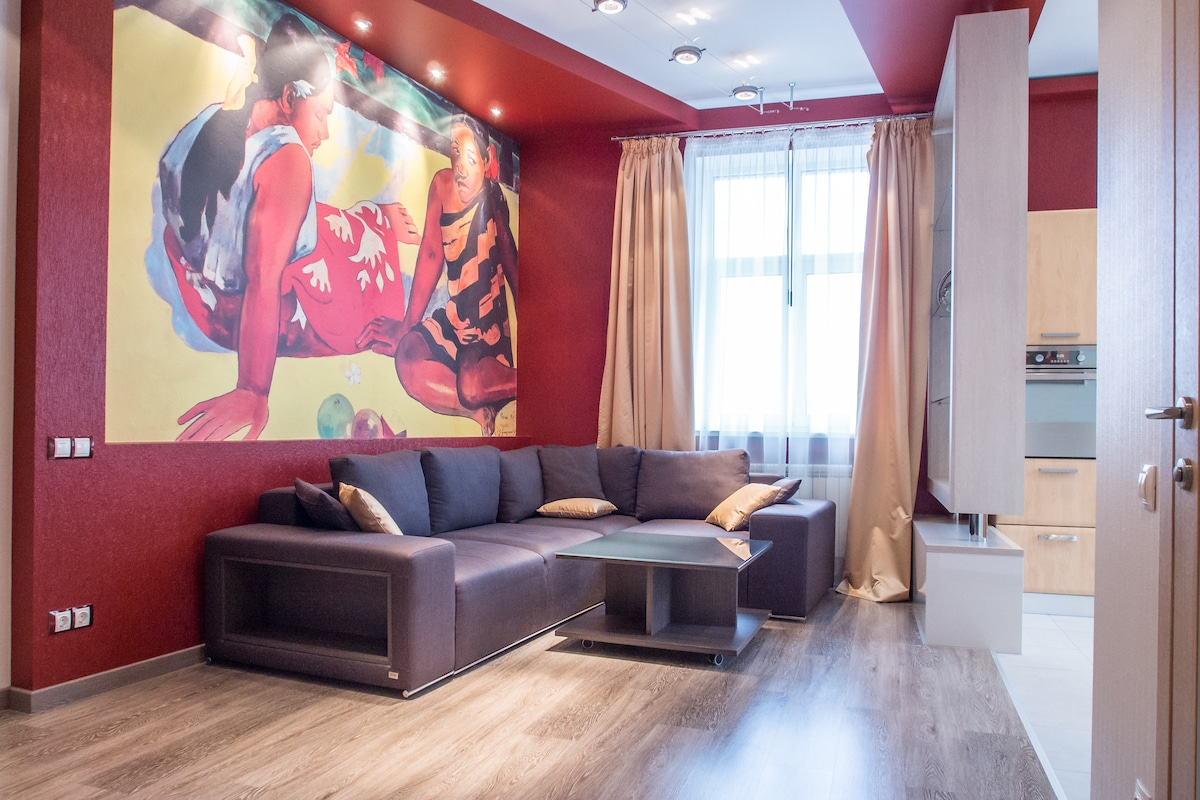 Well decorated livingroom with print of famous Gauguin picture on the wall.