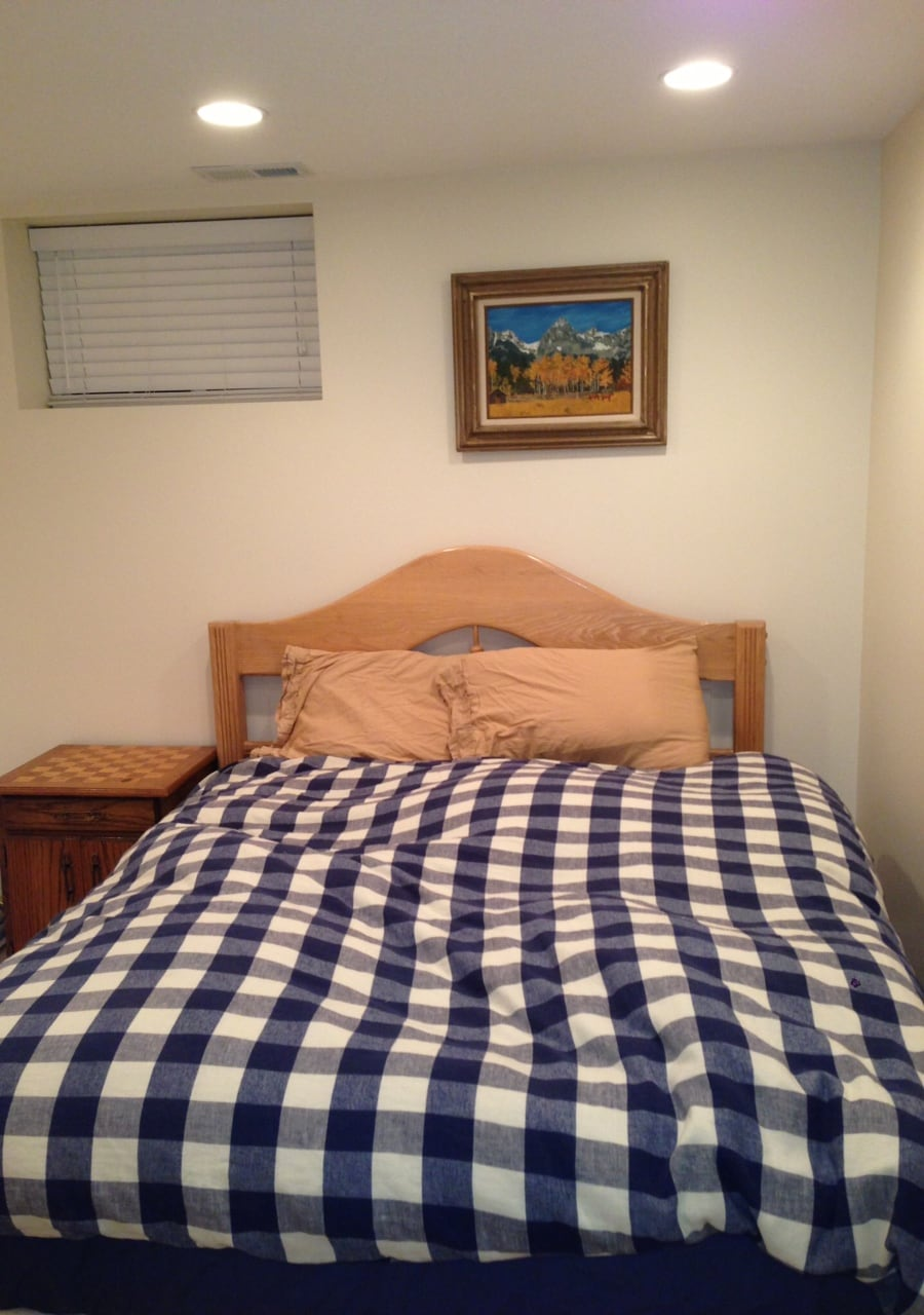 A queen size bed with down comforter in a private bedroom suite on a seperate level of the home.