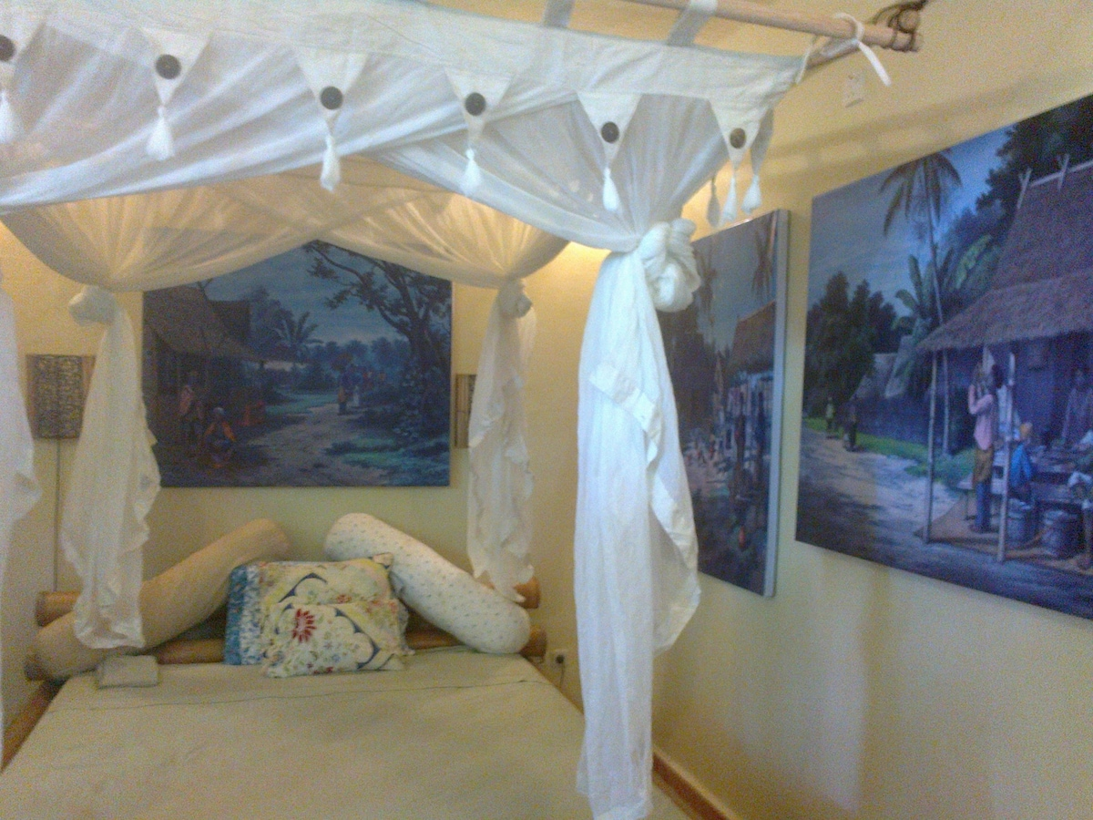 Comfy bed and antique images of Indonesia on the bedroom walls