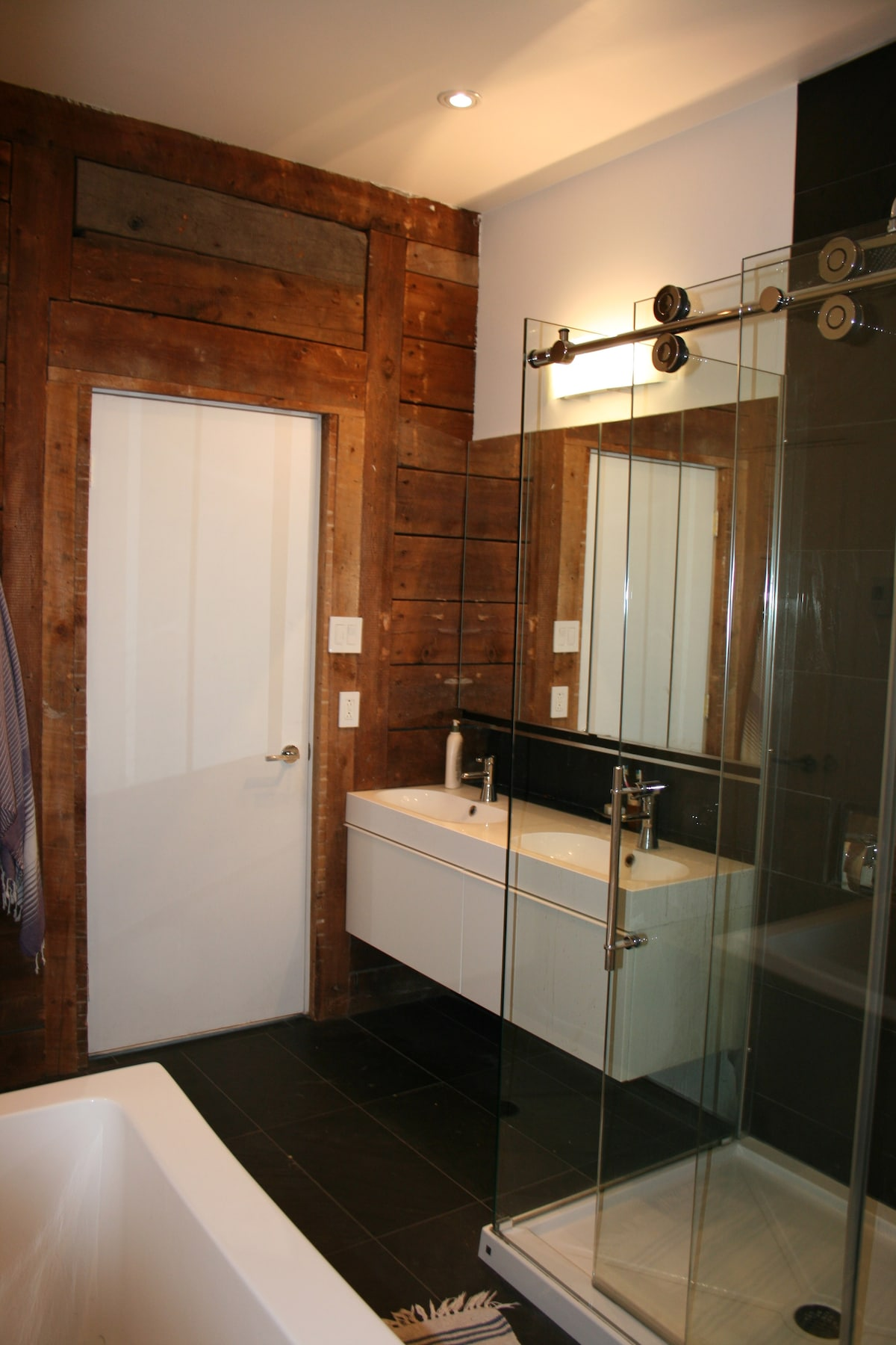 Luxury shower and exposed wood wall