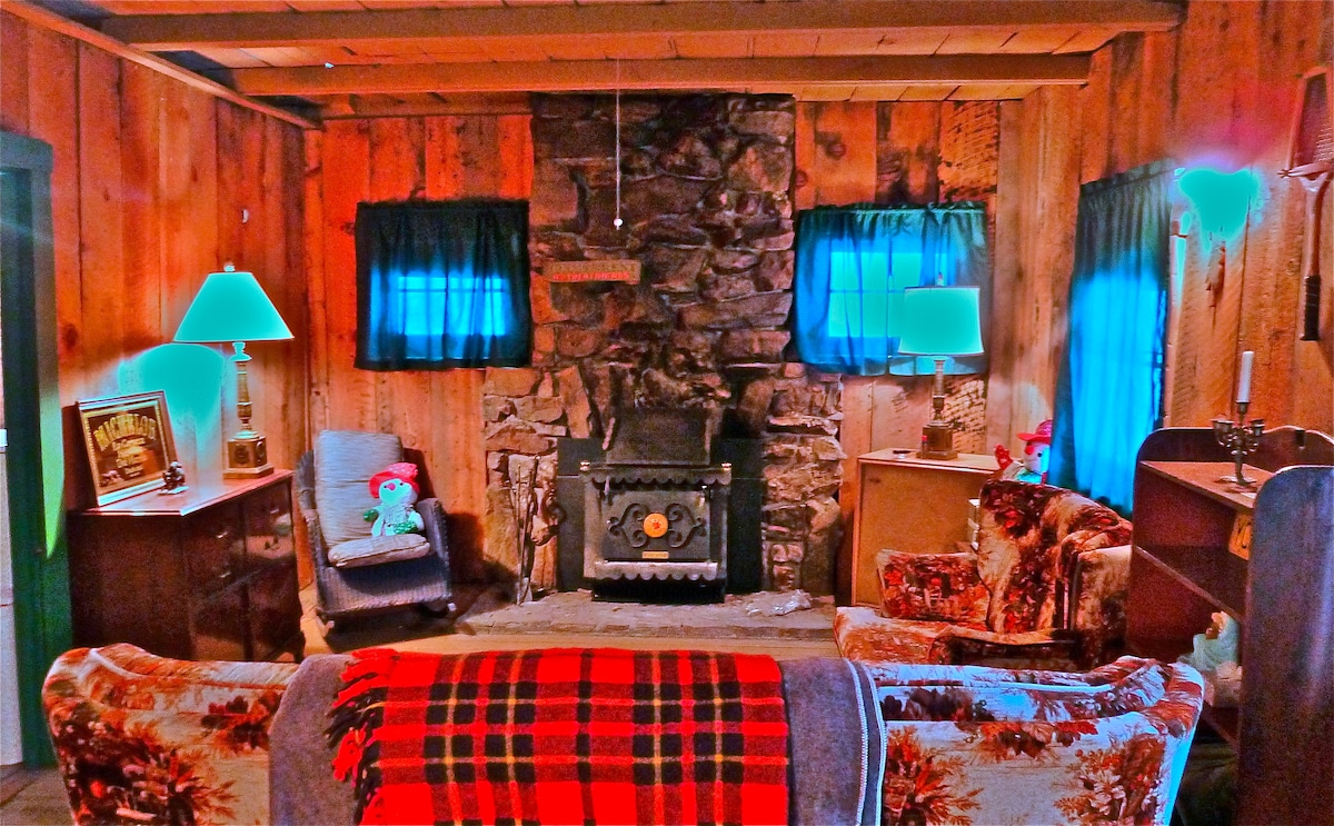 The stone fireplace in the living room houses a wood-burning Franklin stove.