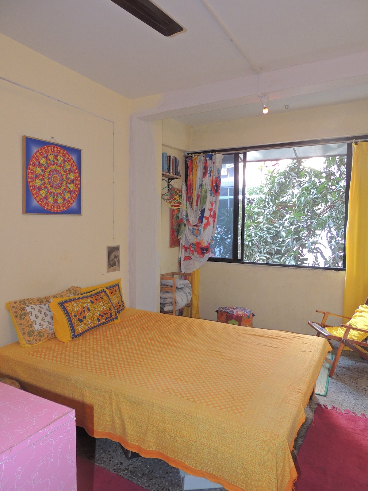 our guest-room with happy yellow mandala, relaxing atmosphere, garden-view, radio, books etc.