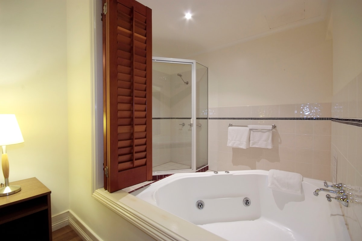 Large two person spa with seperate shower and toilet.  Can someone please bring me a wine?