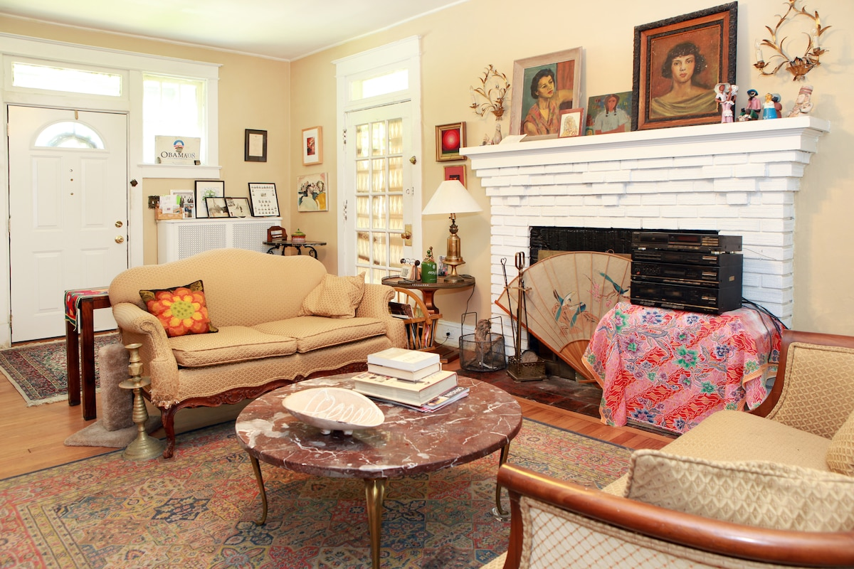 This is the entrance living room. My mother was an artist.  The pictures over the mantle are of me and of her. I collect other artists' paintings.