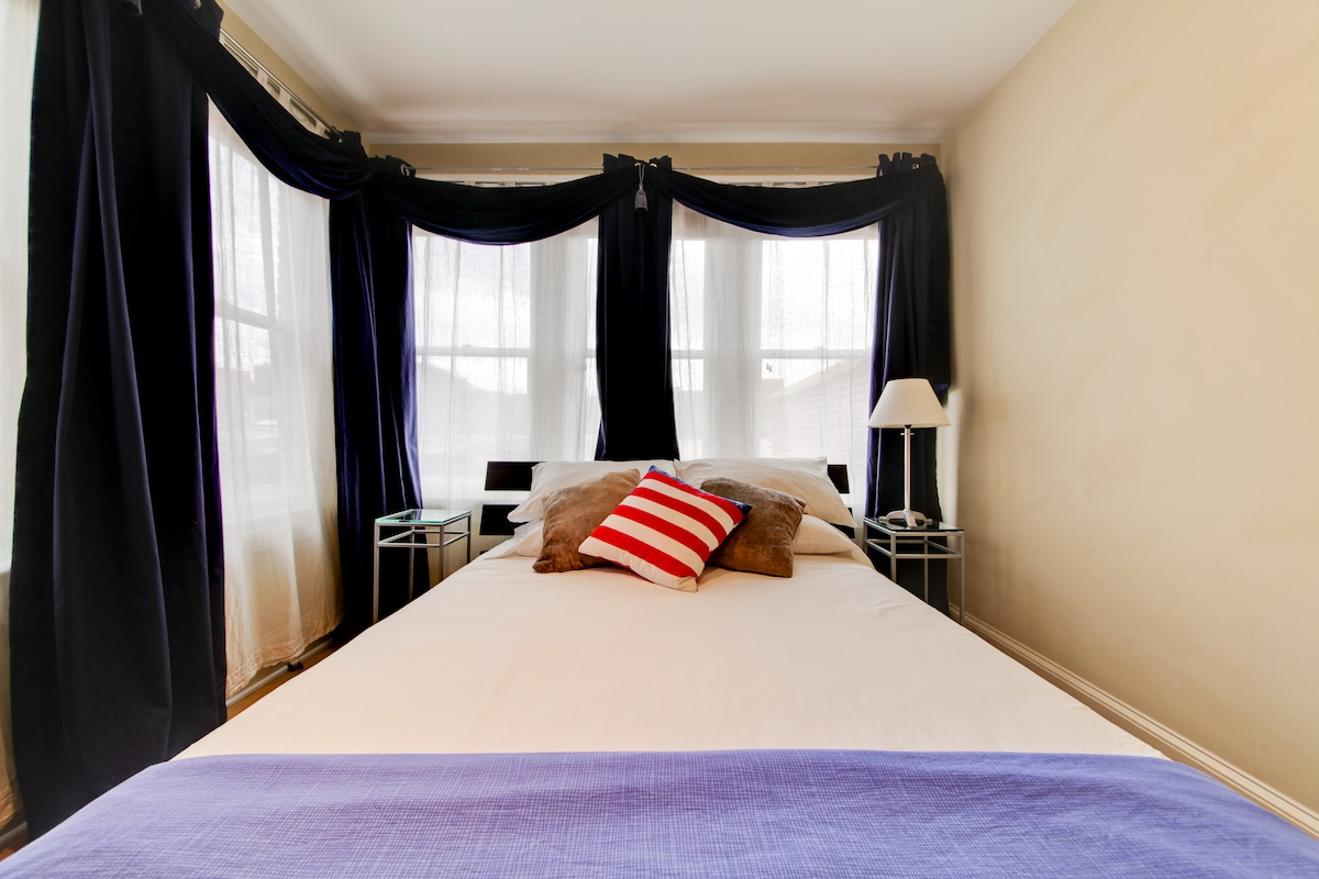 Queen bed with lots of windows to greet the day!