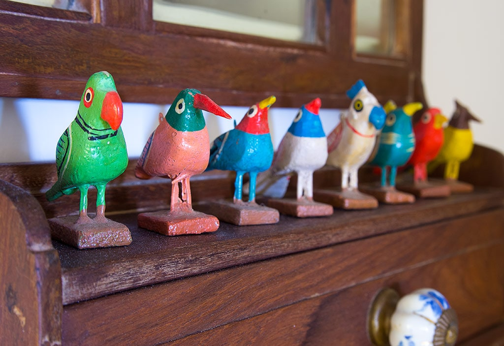 Rosie's collection of hand painted wooden birds singing on the looking glass shelf.