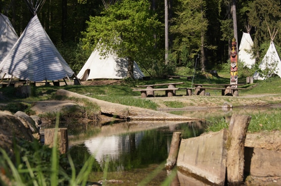 some of our tipis right next to a stream/pond where children love to play...