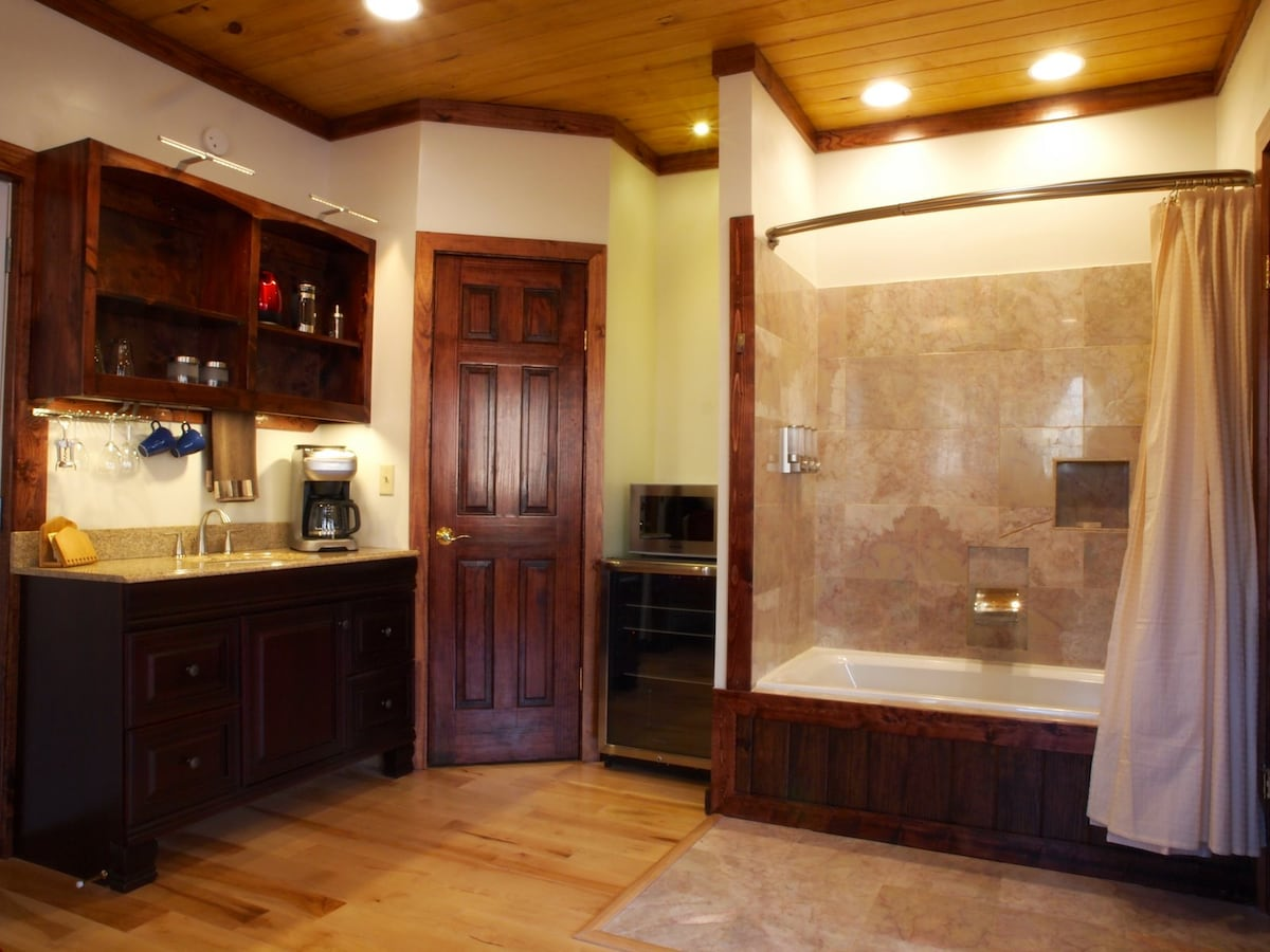 Jacuzzi, closet, coffee station, wet bar with glass front fridge.