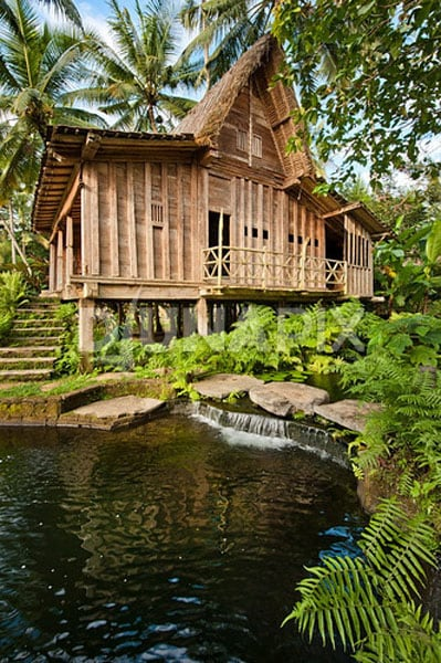 The rice  house stands on the verge of a natural swimming pool