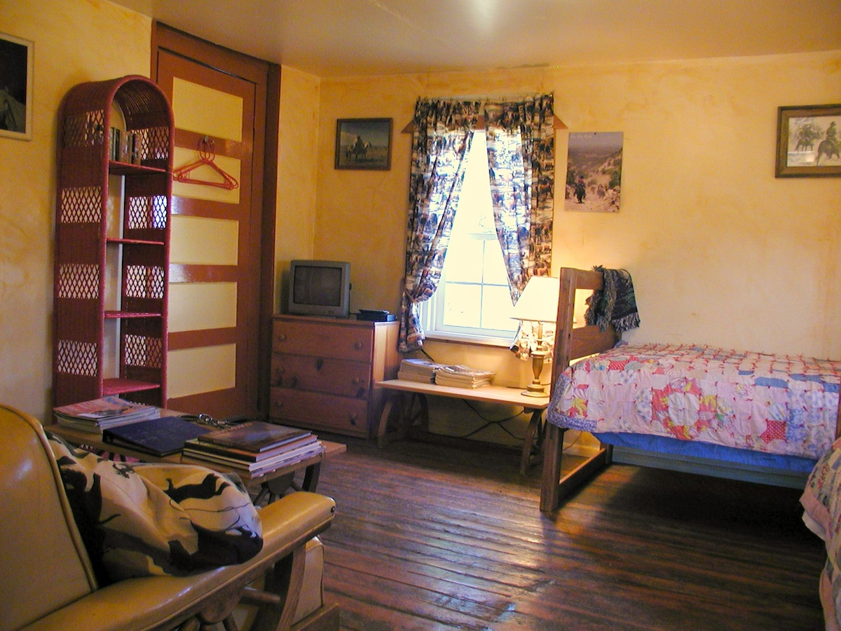 Cow Camp, 2 twin beds to the right, antique Wagon Wheel sofa to left