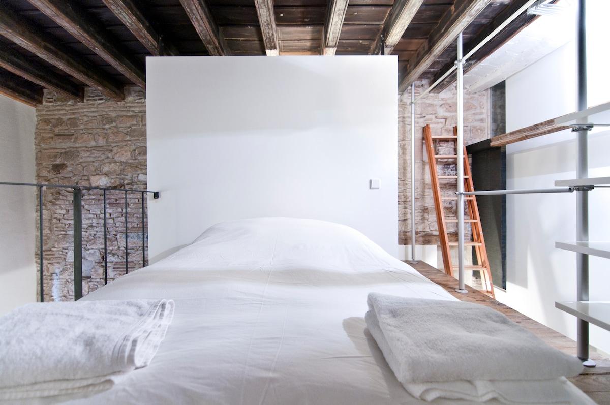 tras la pared de la cama se encuentra el baño y al fondo a la derecha la escalera de acceso al altillo
