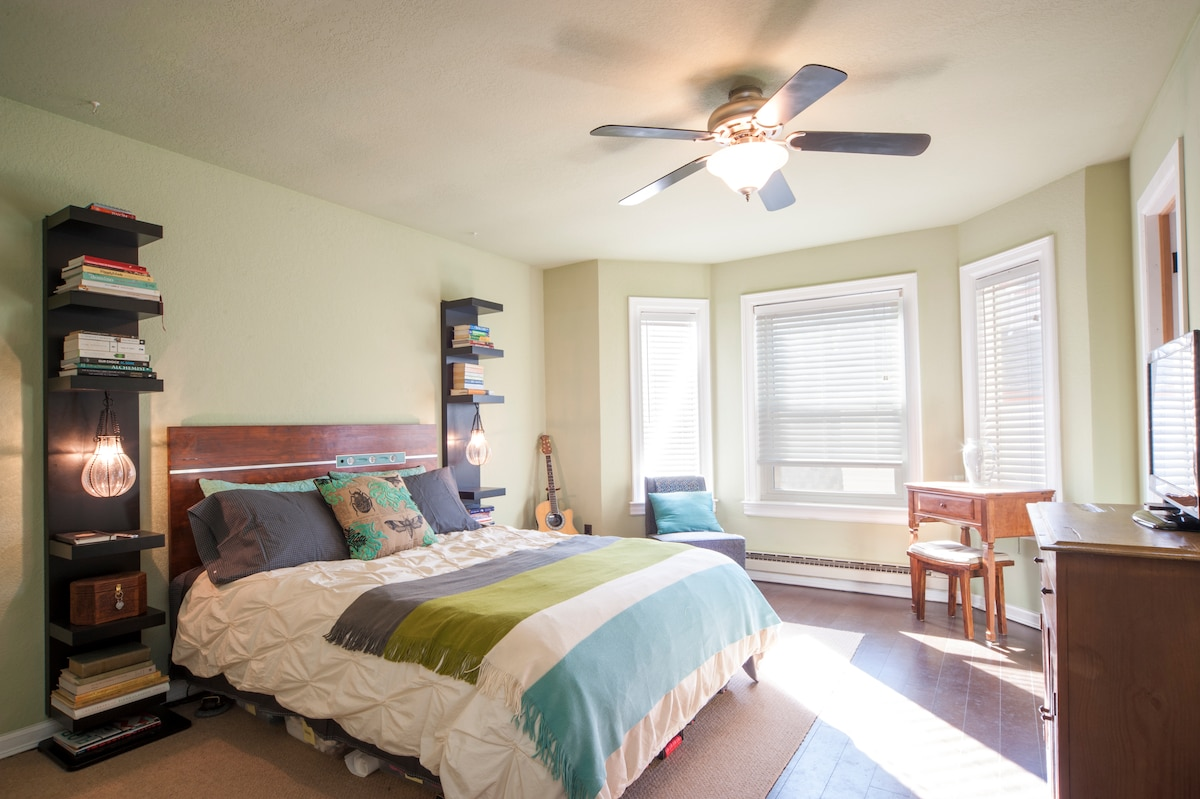 """Sitting area in master bedroom with writing desk and 32"""" HDTV."""